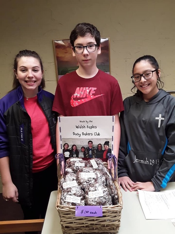 three students posing for a photo with prepared baked goods in a bake sale