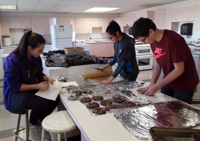three students hard at work in a kitchen preparing a baked good